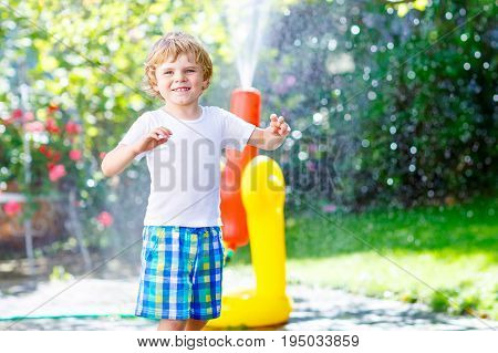 Funny little kid boy playing with a garden hose sprinkler on hot and sunny summer day. Child having fun with sprinkling water, drops rain. Outdoors leisure wth water for children. Rain rubber boots