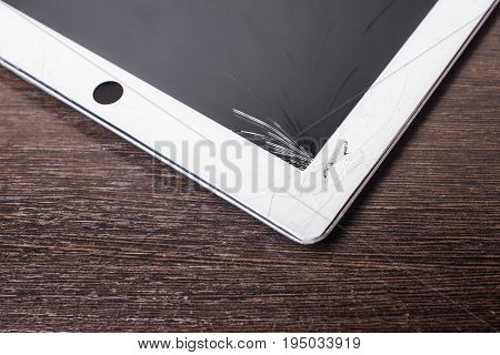 White tablet with broken screen glass on wooden background