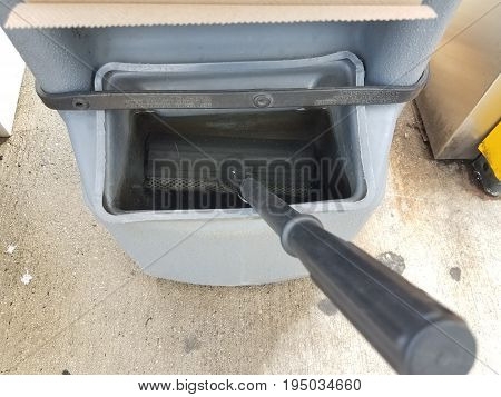 container with squeegee and cleaning fluid at gas station