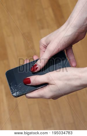 Female hands holding broken smartphone with cracked display