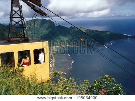 Tourists ride a yellow cable car, to the top of Mount Alava, for a panoramic view of Pago Pago Harbor, and the island of Tutuila, in American Samoa.