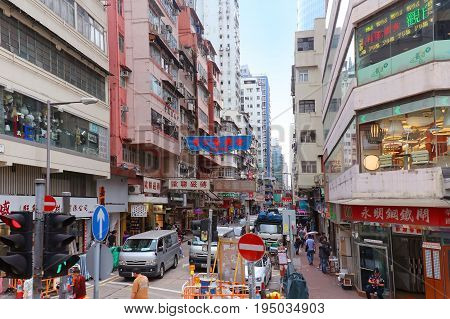 HONG KONG CHINA - APRIL 28; Busy crowded street in Hong Kong with many pedestrians walking around in Hong Kong China - April 28 2017: Typical Hong Kong tall buildings architecture and narrow crowded street.