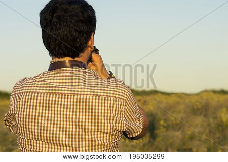 Young professional man with DSLR camera shooting outdoor.