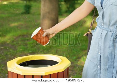 Young woman throwing plastic cup in litter bin outdoors