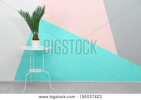 Trendy white table and plant near wall with mint color