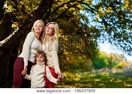 Portait of happy smiling girls posing with little sister in autumn park