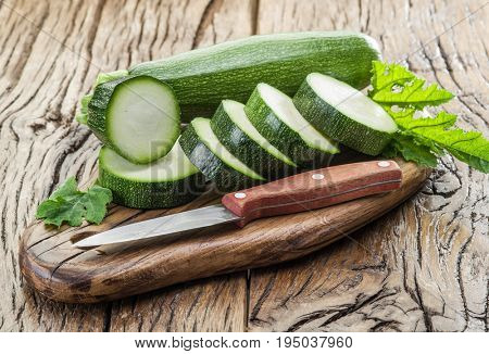 Zucchini with slices on a wooden table.