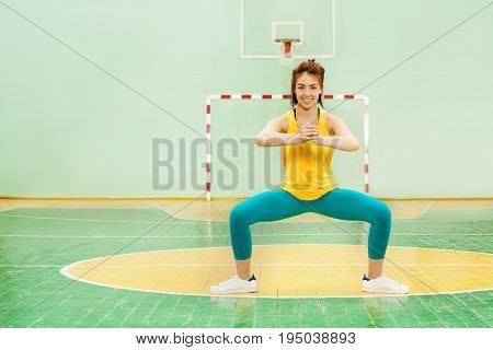Portrait of sporty Asian girl standing in sumo squat position, working out in gymnasium poster