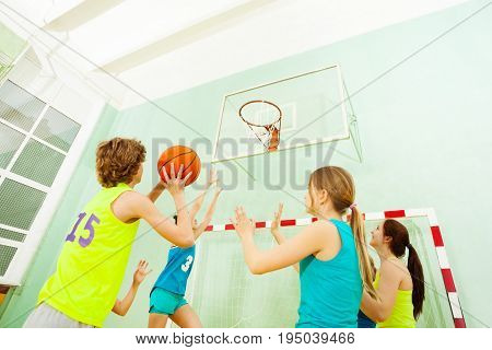 Teenage girls defending against boy throwing ball into the basket during basketball match in gymnasium
