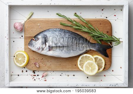 Fresh dorado or gilthead bream cooking with lemon, garlic, herbs and spices on white wooden background