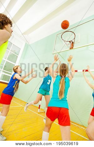 Portrait of teenage girls in sport uniform playing basketball, throwing the ball into the basket