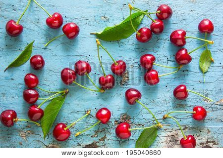 Sweet fresh cherries background. Scattered cherries on blue rustic wood pattern with copy space. Cherry fruit backround. Garden fresh organic cherries at wooden table top view. Food background.