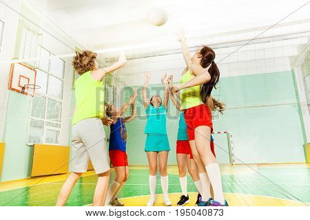 Low angle view of teenage volleyball players striking the ball over the net in gymnasium