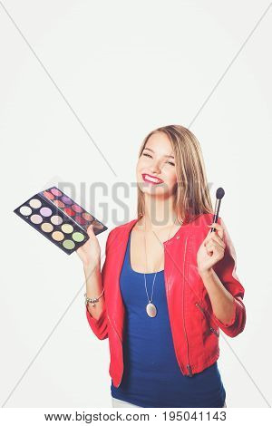 Young beautiful woman holds in one hand and a palette with paint and shadows for makeup, second hand brush for makeup