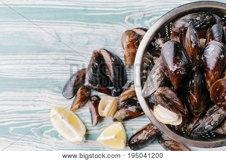 Shell of washed mussels in a colander on a wooden background. Top view.