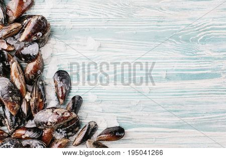 Mussel shells and slices of lemon on a wooden background. Top view. Copy space.