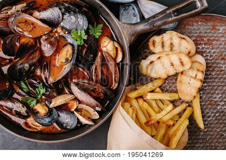 Mussels in a frying pan in tomato sauce, French fries and croutons on a dark background.