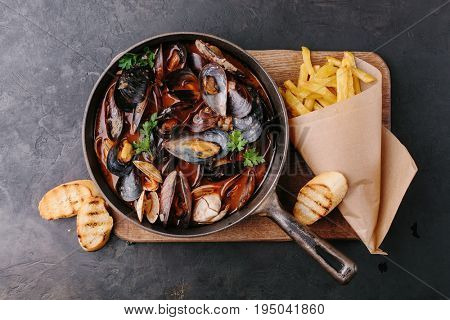 Mussels in a frying pan in tomato sauce, French fries and croutons on a dark background. Top view.