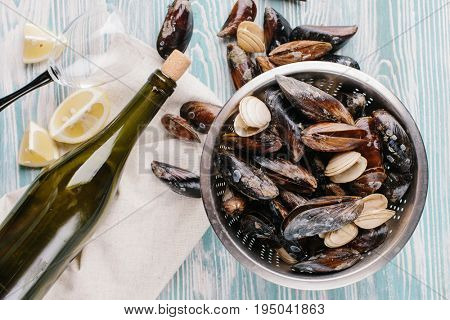 Shells of washed mussels in a colander and slices of lemon and a bottle of wine on a wooden background. Top view.
