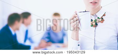 Attractive business woman sitting at office desk, holding a cup of coffee.