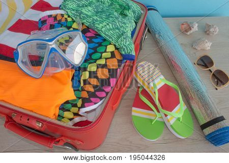 Open suitcase with clothes and personal things packed for travelling. Travel and vacations concept. Open traveler's bag with clothing accessories