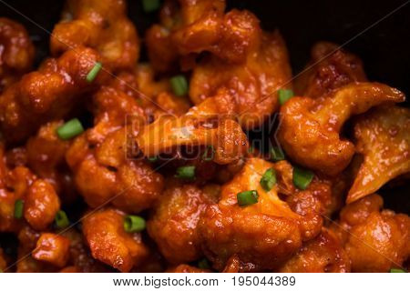 Gobi Manchurian dry - Popular street food of India made of cauliflower florets in a frying pan, selective focus