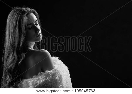 sad woman with bare shoulders in fur on black background, monochrome