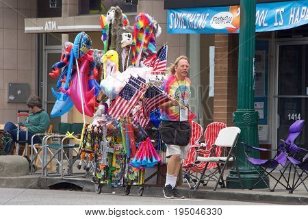 Alameda CA - July 04 2017: The Alameda 4th of July Parade is one of the largest and longest Independence Day parade in the nation. Vendors walk along Park St to sell their products to the crowd.