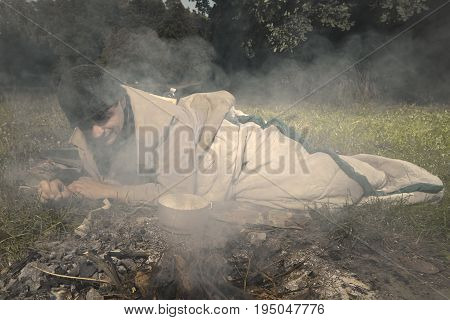 Vagabond young man sleeping in park near illegal fire place