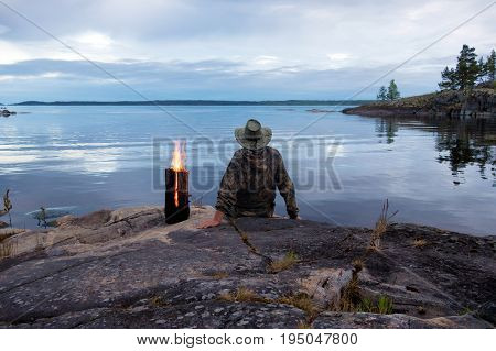 A man sits on the shore of a large lake on a large rock near a burning Finnish candle. In the background there is an evening landscape of a lake and a stony shore.