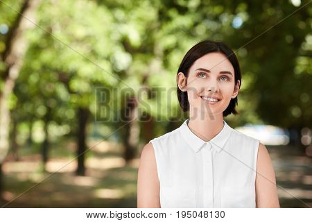 A cheerful young woman on a natural background. A beautiful brunette business lady smiling and walking in a forest in summer. A confident, happy and elegant girl outdoor. A beautiful girl looking up.