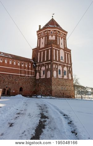 Mir Castle in Minsk region is ancient heritage of Belarus. UNESCO World Heritage. Winter scene with snow and tower backlit