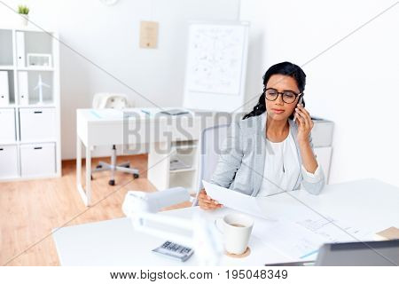 business, technology, communication and people concept - businesswoman with papers calling on smartphone at office