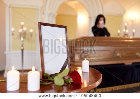 people and mourning concept - photo frame with black ribbon, candles and woman crying near coffin at funeral in church