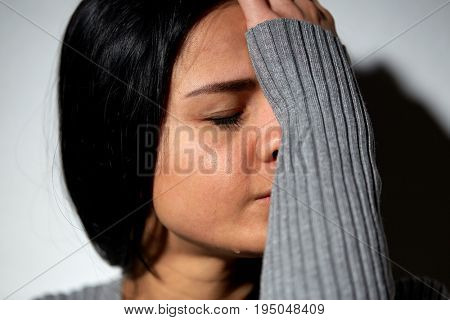 people, grief and domestic violence concept - close up of unhappy crying woman