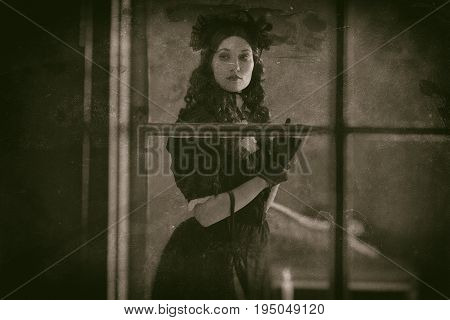 Worn Wet Plate Photo Of Vintage Victorian Woman In Black Dress Standing Behind Window With Candlelig