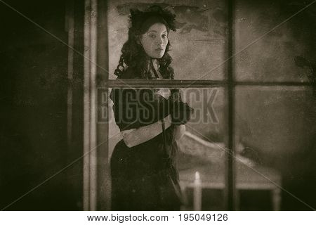 Worn Wet Plate Photo Of Victorian Woman In Black Dress Standing Behind Window With Candlelight.