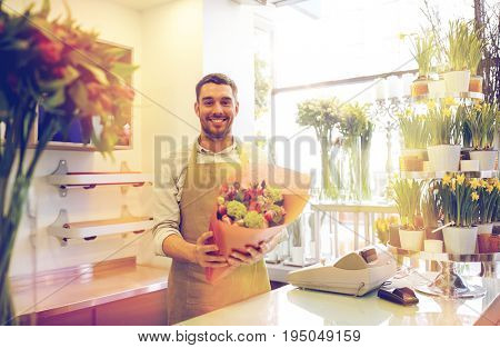 people, business, sale and floristry concept - happy smiling florist man with bunch at flower shop