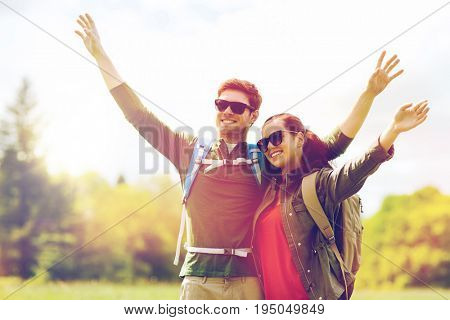 travel, hiking, backpacking, tourism and people concept - happy couple with backpacks waving hands and walking along country road outdoors