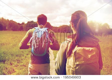travel, hiking, backpacking, tourism and people concept - close up of couple with backpacks walking along country road