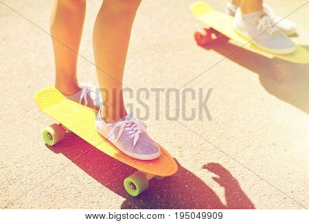 skateboarding, leisure, extreme sport and people concept - close up of young woman legs riding short modern cruiser skateboard on road