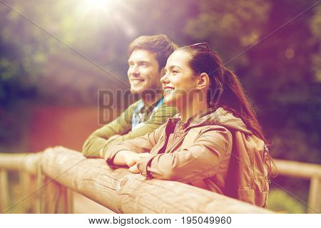 travel, hiking, backpacking, tourism and people concept - smiling couple with backpacks on bridge in nature