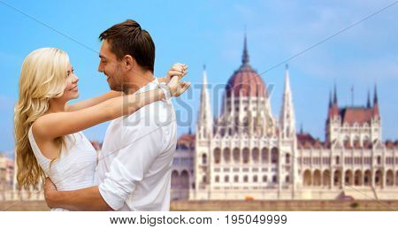 travel, tourism and summer holidays concept - happy couple hugging over house of parliament in budapest background