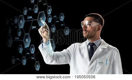 science, chemistry and people concept - male doctor or scientist in white coat and safety glasses touching virtual projection of chemical formula over black background