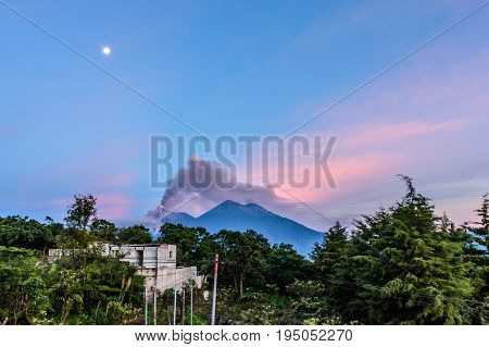 Lava & smoke spurt from erupting Fuego volcano next to Acatenango volcano at dawn under a full moon near Antigua, Guatemala, Central America