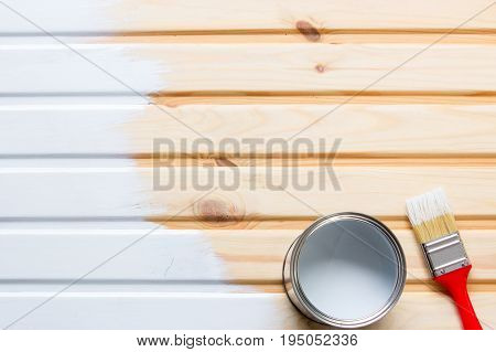 Brush and a metal can with paint on wooden boards. Painted boards with white paint. Copy space and paste text. mockup