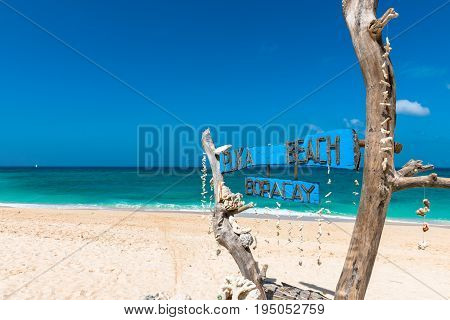 BORACAY WESTERN VISAYAS PHILIPPINES - JANUARY 14 2015: Wooden board written Puka Beach the name of the beautiful beach of the island of Boracay. Blue sky in a summer season.