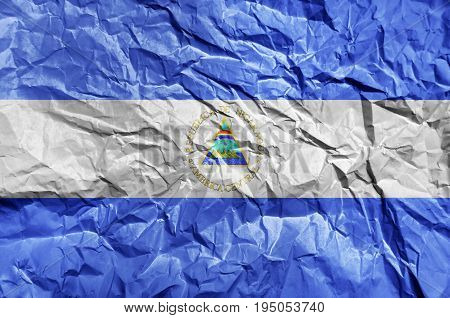 Nicaragua flag painted on crumpled paper background