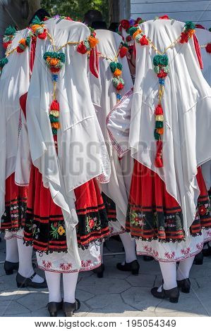 Bulgarian girls dressed in traditional folk costumes with multicolored embroidery.