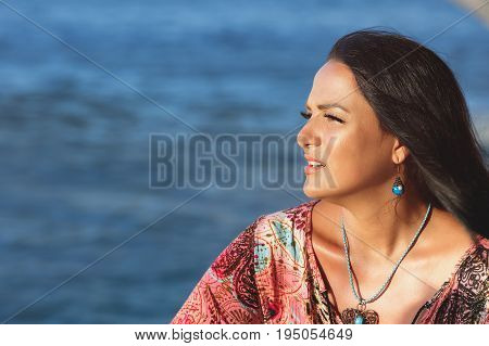 Beautiful woman sitting on  the beach and watching the ocean. Side view of beautiful  woman in dress sitting on the beach at sunset and looking away